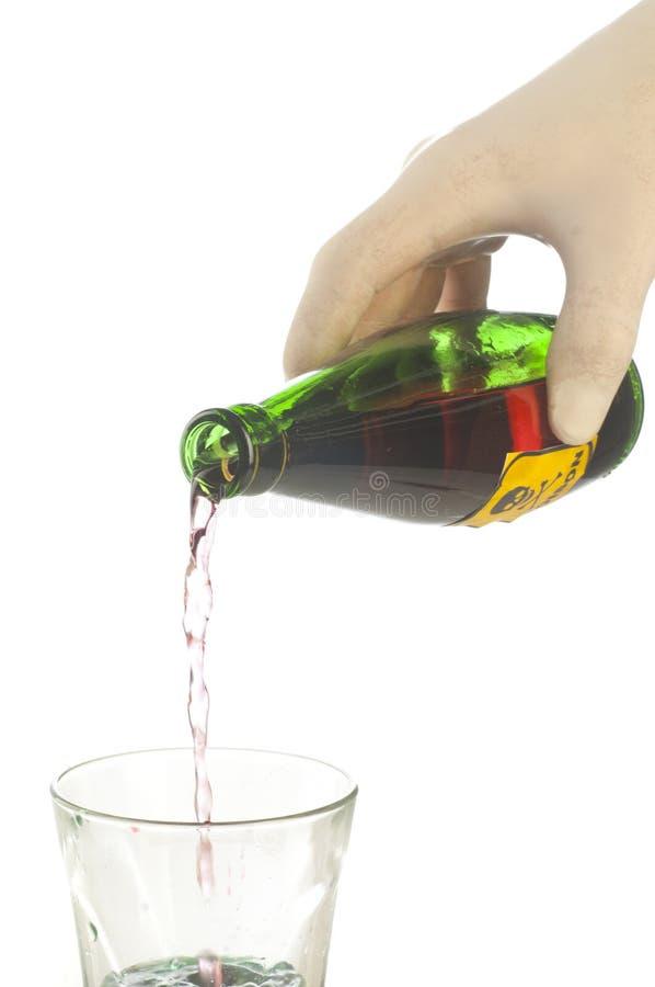 有骷髅图的绿色毒物瓶在手边 图库摄影