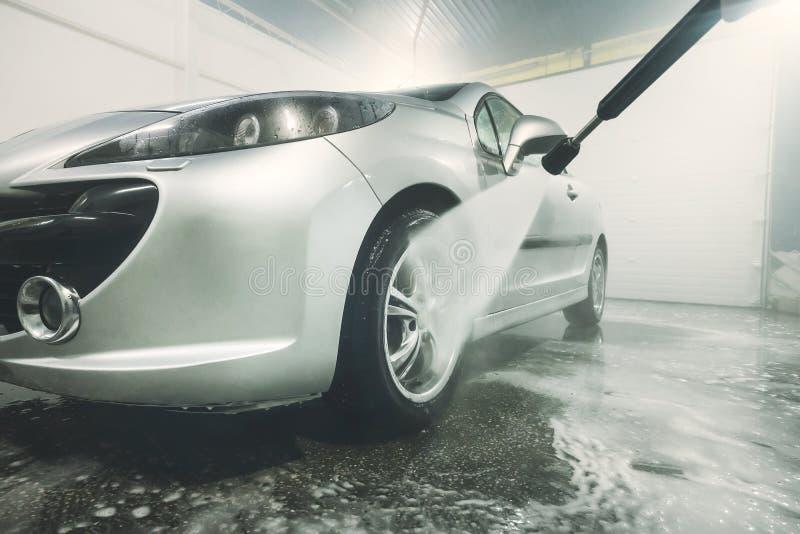 有高压喷水或喷气机的人清洗的车 洗车细节 洗涤汽车的前轮 库存照片