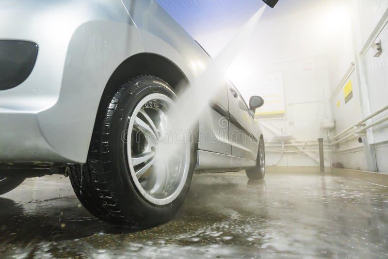 有高压喷水或喷气机的人清洗的车 洗车细节 洗涤汽车的后轮 库存图片