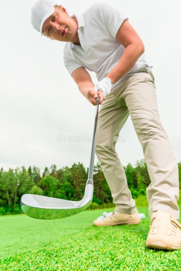 有高尔夫俱乐部的被集中的男性高尔夫球运动员 库存图片