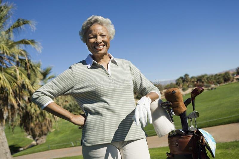 有高尔夫球袋的愉快的资深妇女 免版税库存照片