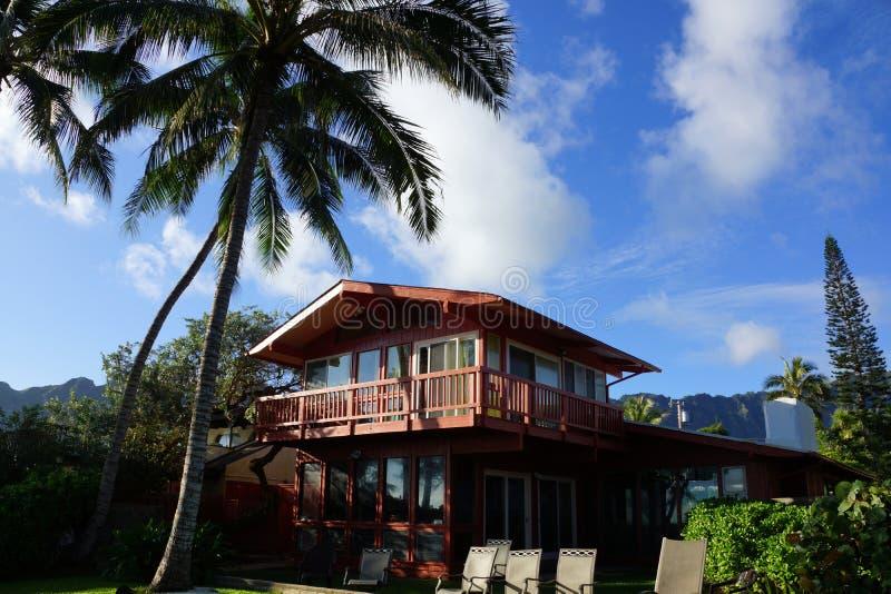 有高椰子树的红色二层的海滨别墅 图库摄影