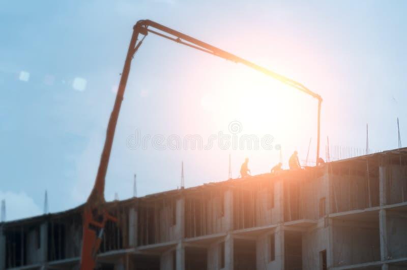 有高楼的建筑工地建设中在一个城市环境里由一台大工业起重机控制了 库存图片