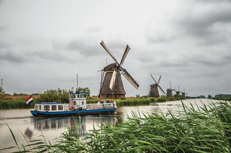 有高灌木、风车和小船的平直的运河在小孩堤防 库存照片