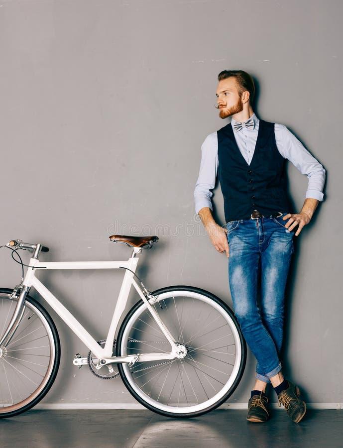 有髭和胡子的一个年轻人是在时兴的现代fixgear自行车附近 牛仔裤和衬衣、背心和蝶形领结行家styl 库存图片