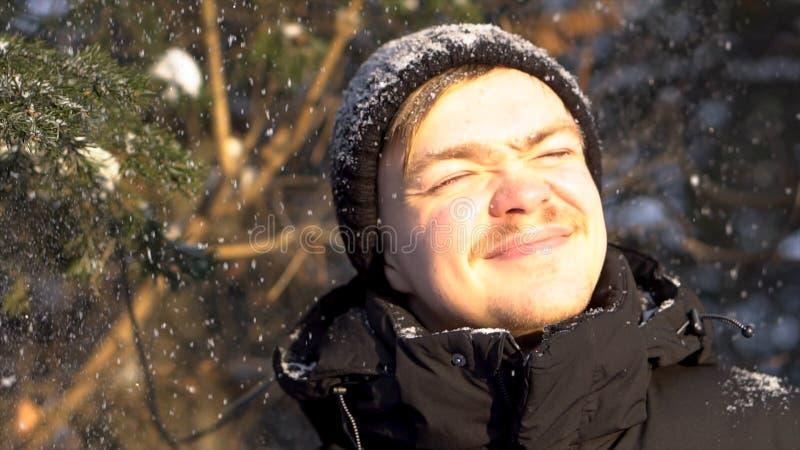 有髭的享受降雪的年轻,微笑的人画象在冬天森林里,斜眼看他的从明亮的太阳的眼睛 库存照片