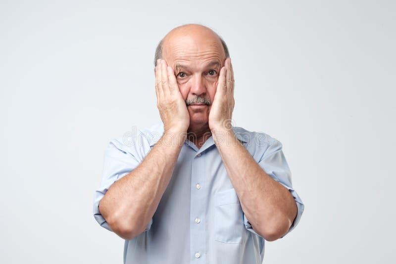 有髭的秃头成熟人在蓝色衬衣遭受犹豫不决 免版税库存照片