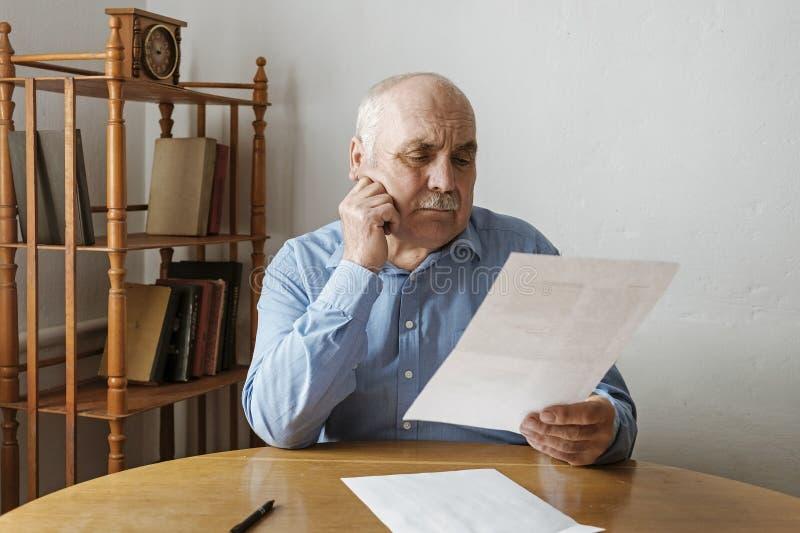有髭读书的年长灰发的人 免版税库存照片