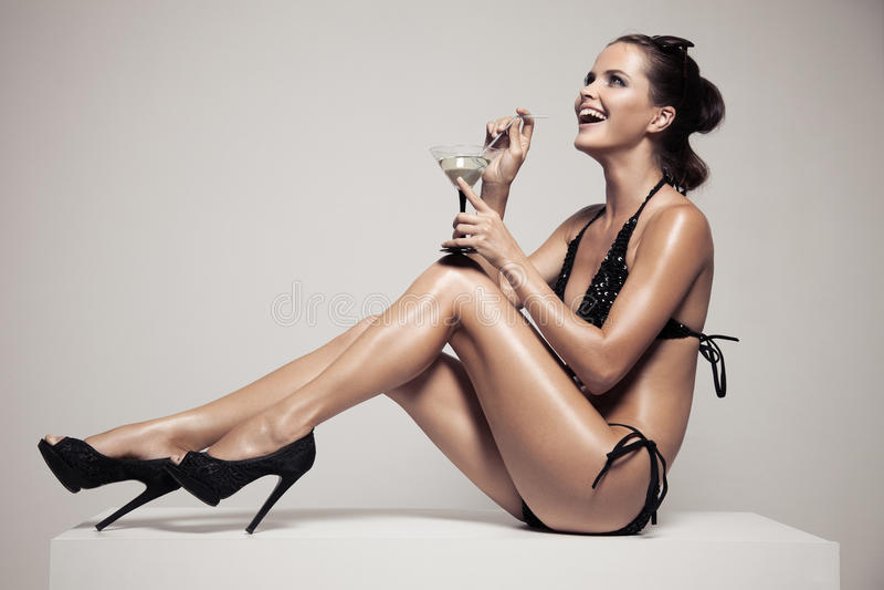 有魅力的美丽的妇女在时髦的黑游泳衣组成 饮料玻璃鸡尾酒 免版税图库摄影