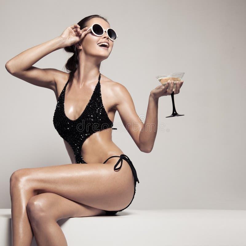 有魅力的美丽的妇女在时髦的黑游泳衣组成 饮料玻璃鸡尾酒 库存图片