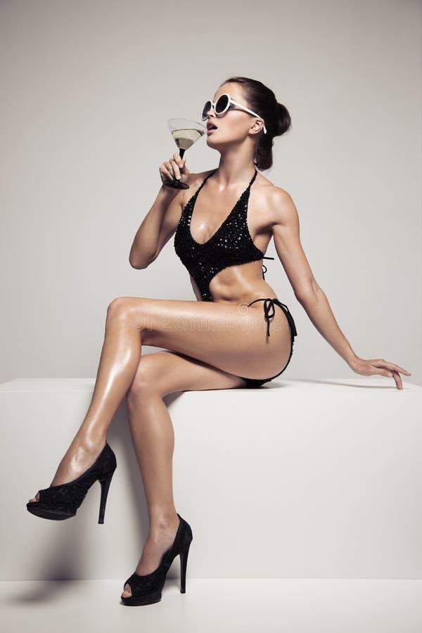 有魅力的美丽的妇女在时髦的黑游泳衣组成 饮料玻璃鸡尾酒 免版税库存照片