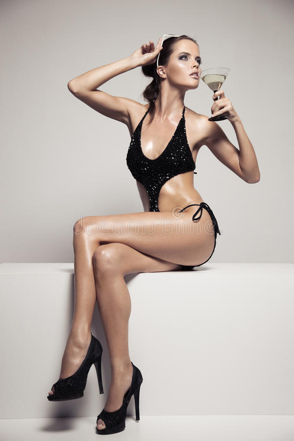 有魅力的美丽的妇女在时髦的黑游泳衣组成 饮料玻璃鸡尾酒 免版税库存图片