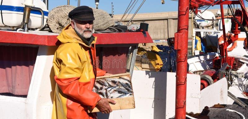 有鱼箱子的一位渔夫在一个渔船里面 免版税库存照片