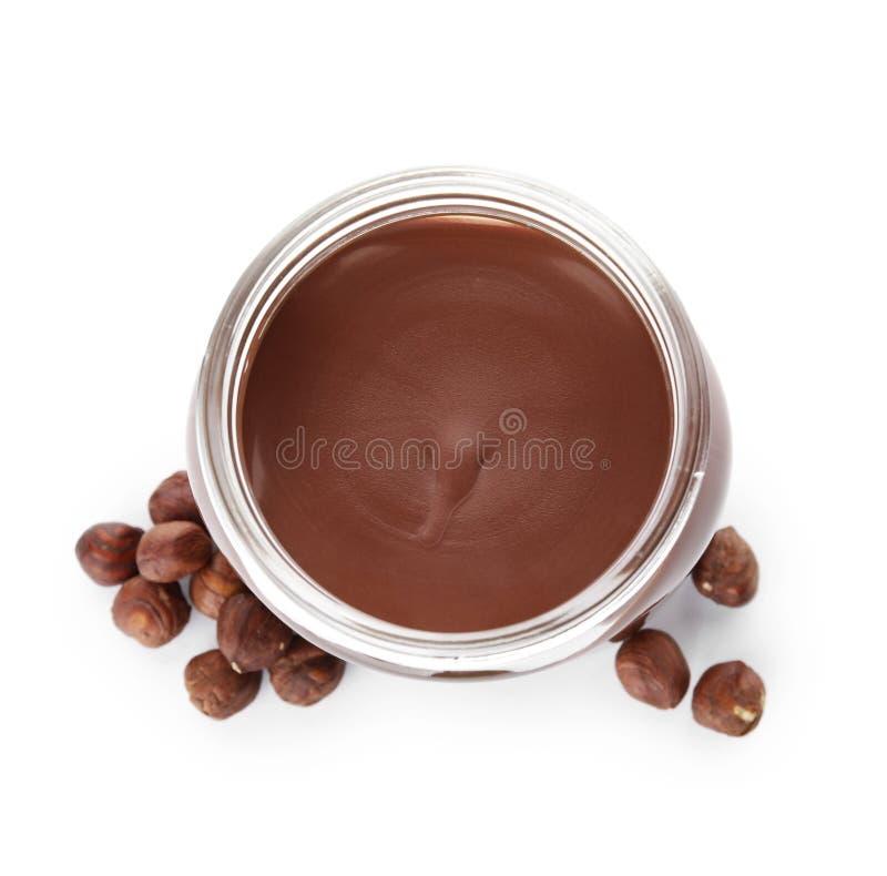 有鲜美在白色隔绝的巧克力奶油和榛子的玻璃瓶子 库存照片