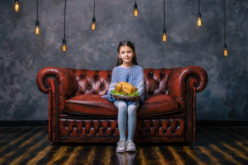 有鲜美炸鸡的饥饿的孩子在手上 免版税图库摄影