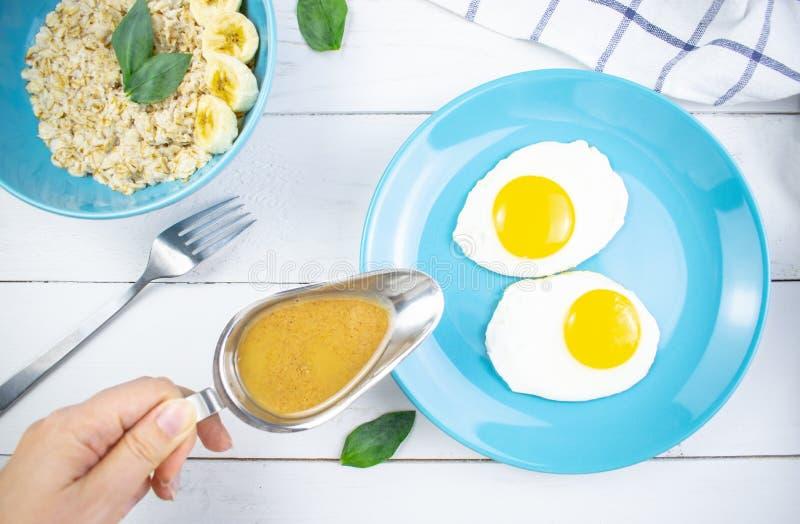 有鲜美燕麦粥和香蕉切片的在白色木背景的板材和荷包蛋 早餐的概念图象,健康 免版税库存图片