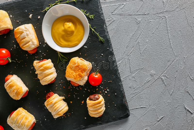 有鲜美腊肠卷和调味汁的板岩板材在桌,顶视图上 免版税库存照片