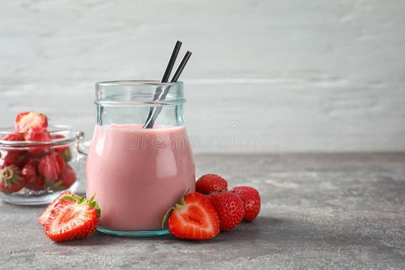 有鲜美草莓圆滑的人的玻璃瓶子 免版税库存图片