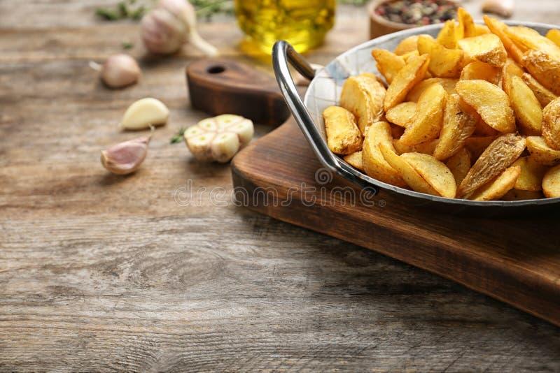 有鲜美被烘烤的土豆楔子的煎锅在桌上 文本的空间 库存照片