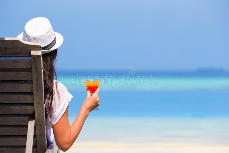 有鸡尾酒杯的少妇在游泳池附近 免版税库存图片