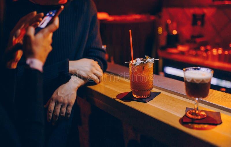 有鸡尾酒照相的妇女从酒吧柜台的在酒吧柜台时髦的edi的夜总会甜水多的鸡尾酒饮料饮料 免版税库存照片