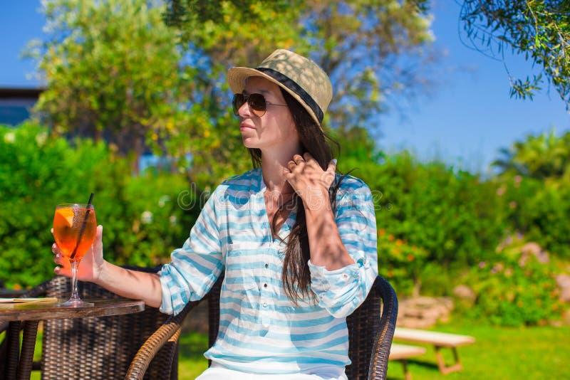有鸡尾酒的年轻美丽的妇女在oitdoor 免版税库存照片