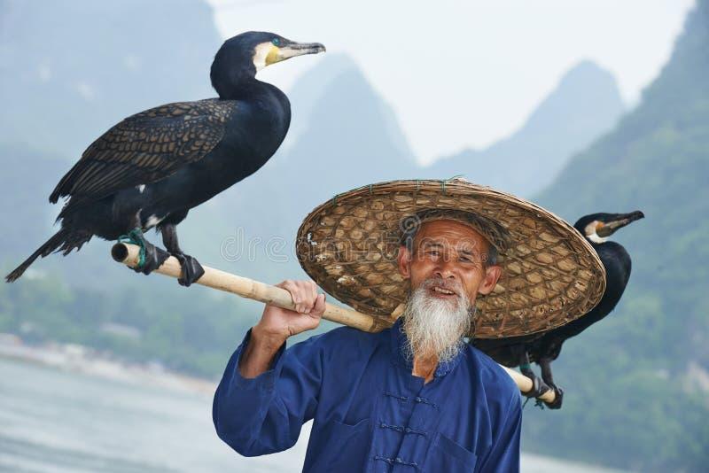 有鸬鹚的中国老人钓鱼的 图库摄影