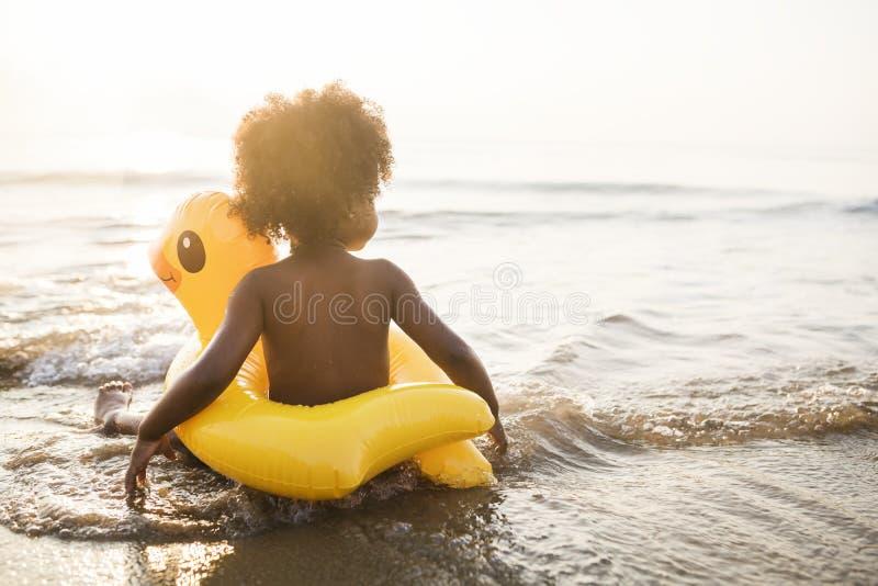 有鸭子管的逗人喜爱的小孩在海滩 库存图片
