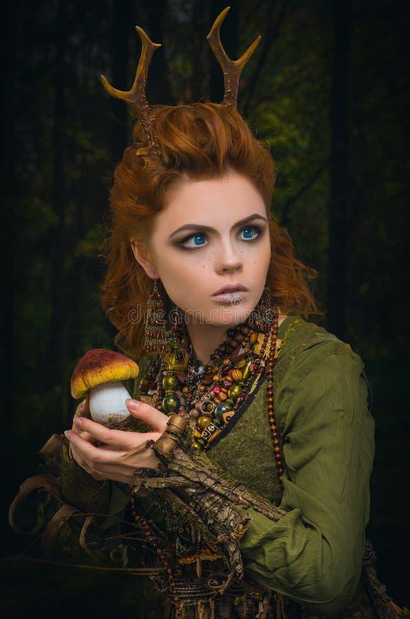 有鹿角的俏丽的森林女孩 免版税库存照片