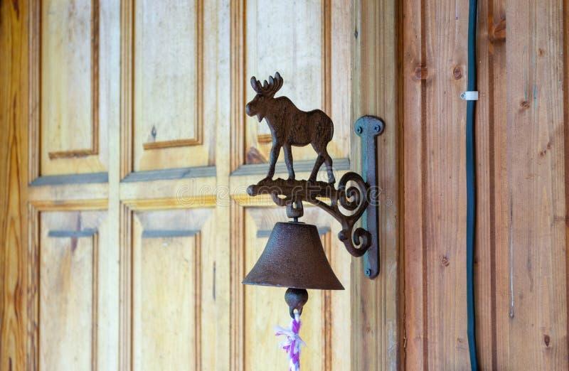 有麋形象和一条白色和紫色绳索的一个老古铜色门铃 免版税库存图片