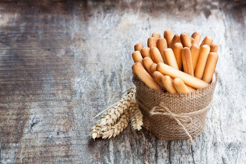 有麦子耳朵的盐味的面包条在木桌上 免版税库存照片
