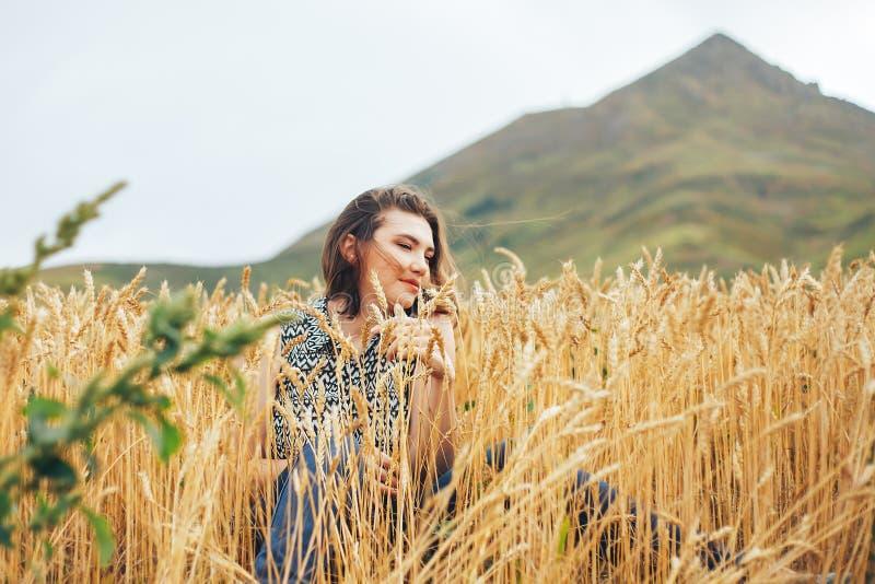 有麦子耳朵的美丽的年轻深色的妇女在麦田 库存图片