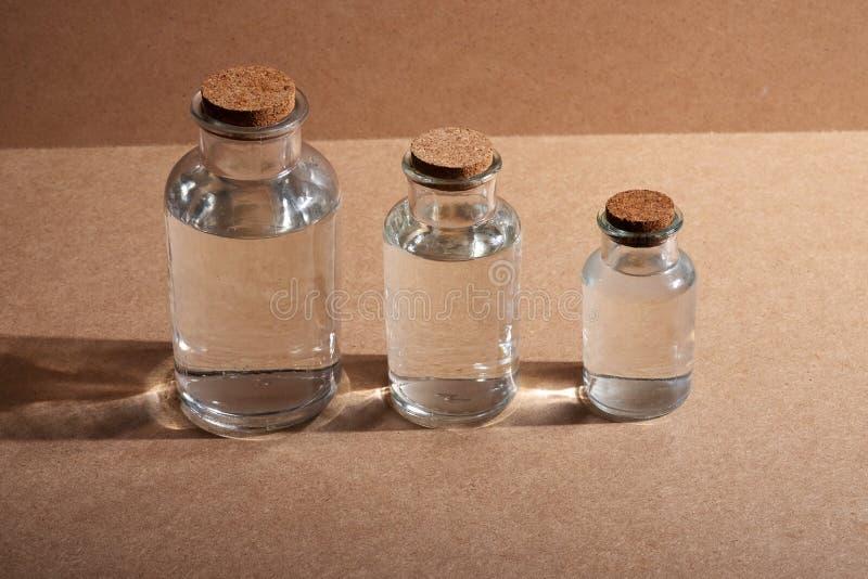 有黄柏盖帽的玻璃瓶反对被烙记的纸板背景或木 免版税库存图片