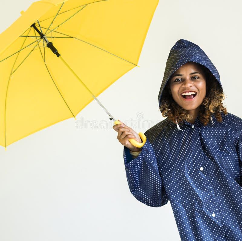 有黄色伞的愉快的女孩 免版税库存图片