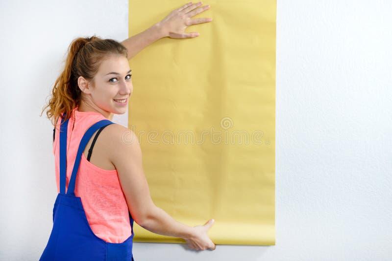 有黄色墙纸卷的少妇  免版税库存照片