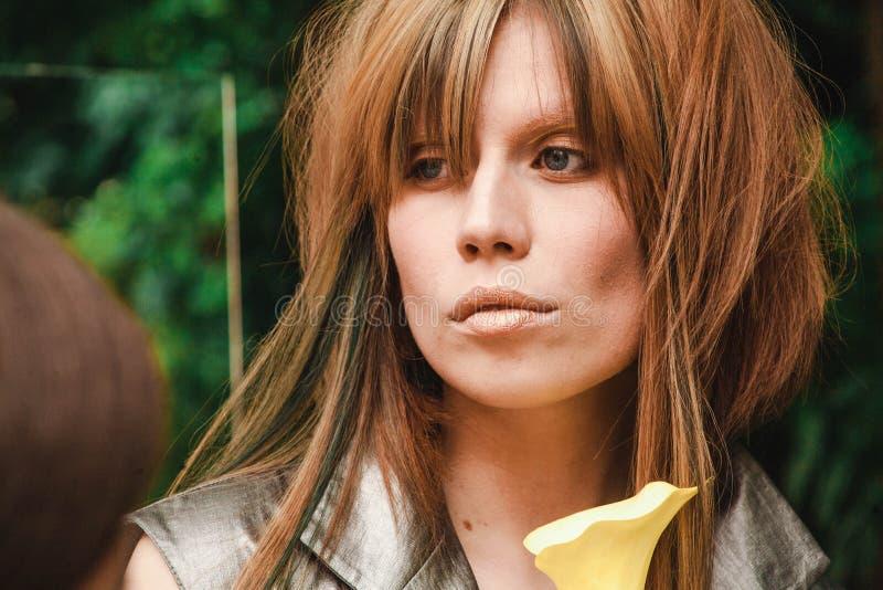 有黄色头发和绿色锁的哀伤的女孩 免版税库存照片