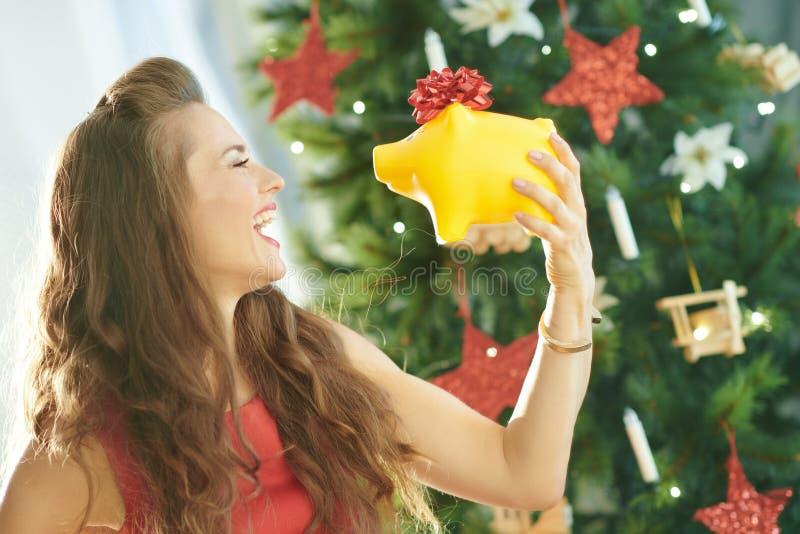 有黄色存钱罐的愉快的时髦妇女在圣诞树附近 免版税库存照片