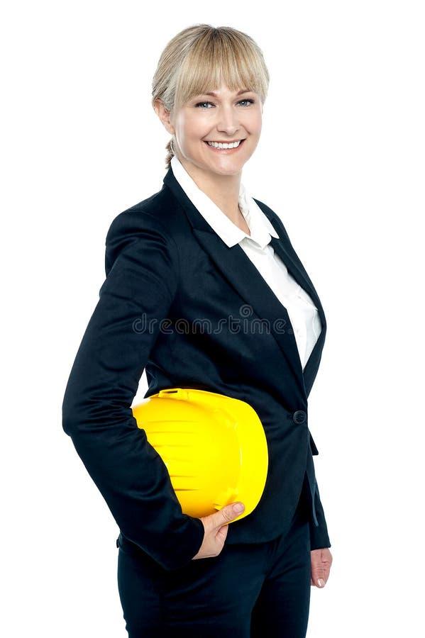 有黄色安全帽的俏丽的企业建筑师在手中 图库摄影