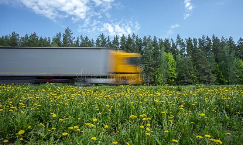 有黄色小室的一辆卡车沿沿森林的路冲,路旁用黄色蒲公英盖 免版税库存照片