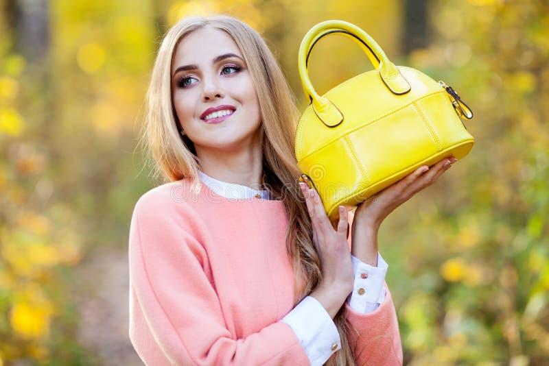 有黄色时兴的袋子的美丽的少妇在秋天自然的手上 库存图片