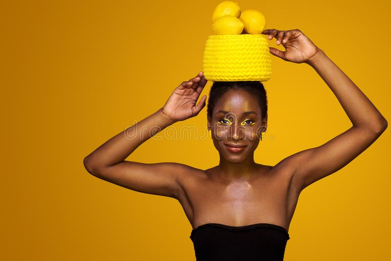 有黄色构成的快乐的年轻非洲妇女在她的眼睛 反对黄色背景的女性模型用黄色柠檬 库存图片