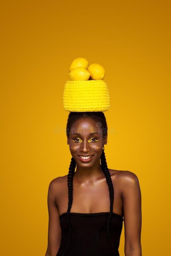 有黄色构成的快乐的年轻非洲妇女在她的眼睛 反对黄色背景的女性模型用黄色柠檬 免版税库存图片