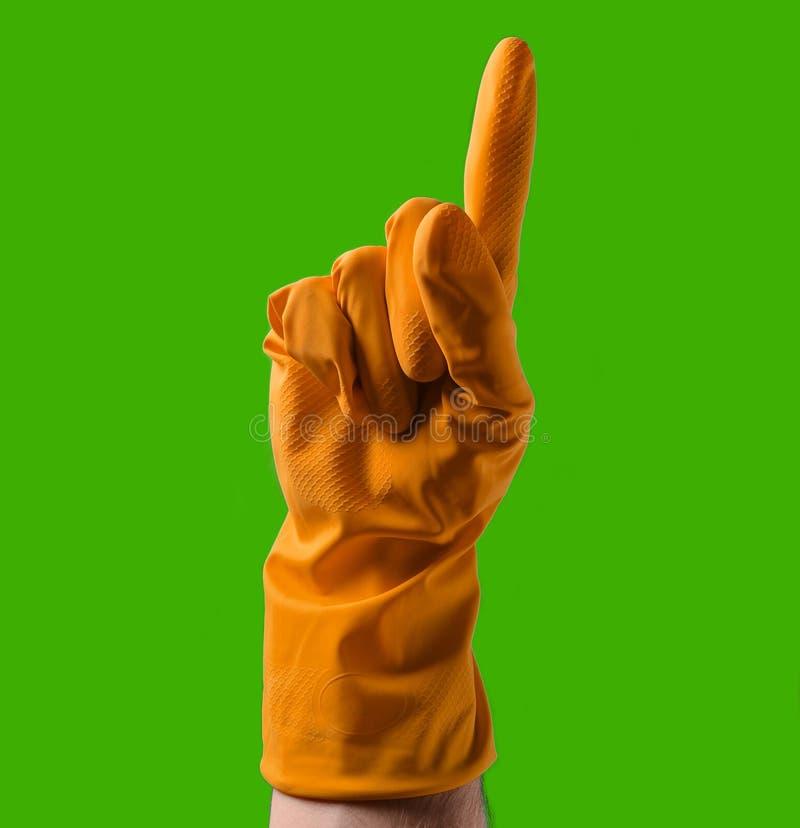 有黄色橡胶手套的手向上指向与食指, 免版税库存照片