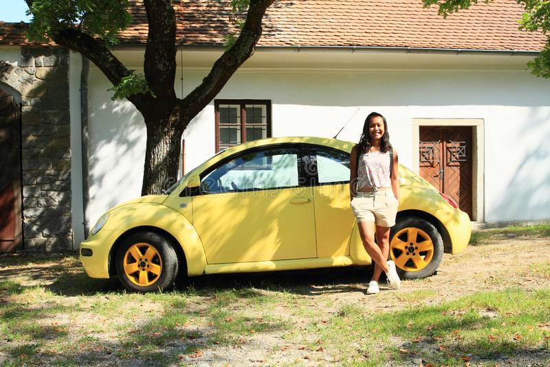 有黄色汽车新的甲虫的女孩 免版税库存图片