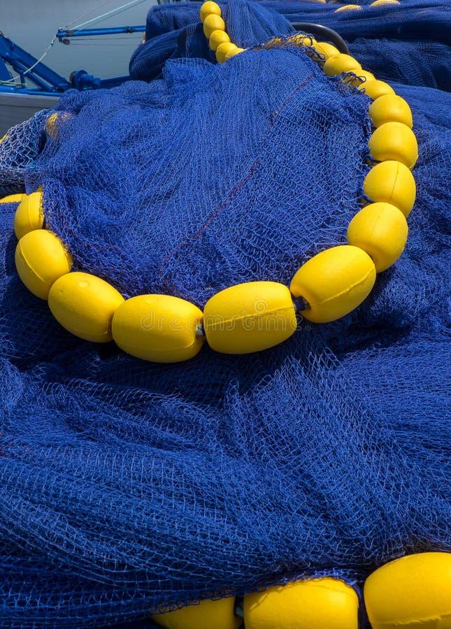 有黄色浮游物的垂直的深刻的蓝色鱼网 免版税库存照片