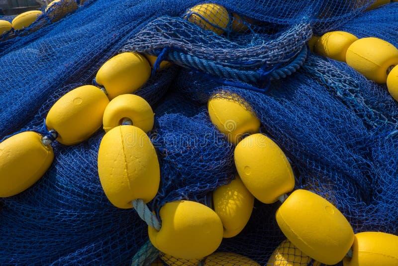 有黄色浮游物的深刻的蓝色鱼网 免版税图库摄影