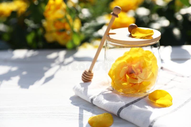 有黄色玫瑰和蜂蜜浸染工的玻璃瓶子在白色木桌上在开花的庭院里 免版税库存照片
