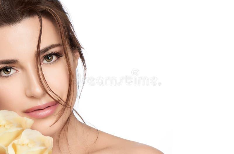 有黄色玫瑰的美丽的年轻女人 Skincare和健康整容术概念 库存图片