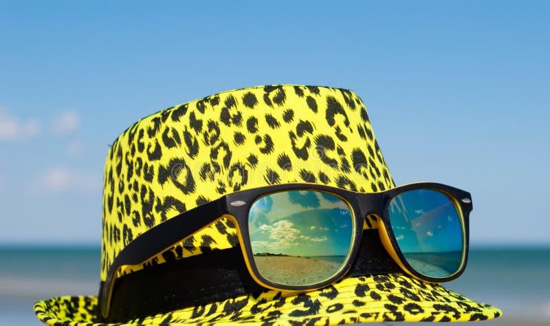 有黄色玻璃变色蜥蜴透镜的明亮的黄色帽子在蓝天背景与海的玻璃反射的 免版税库存照片