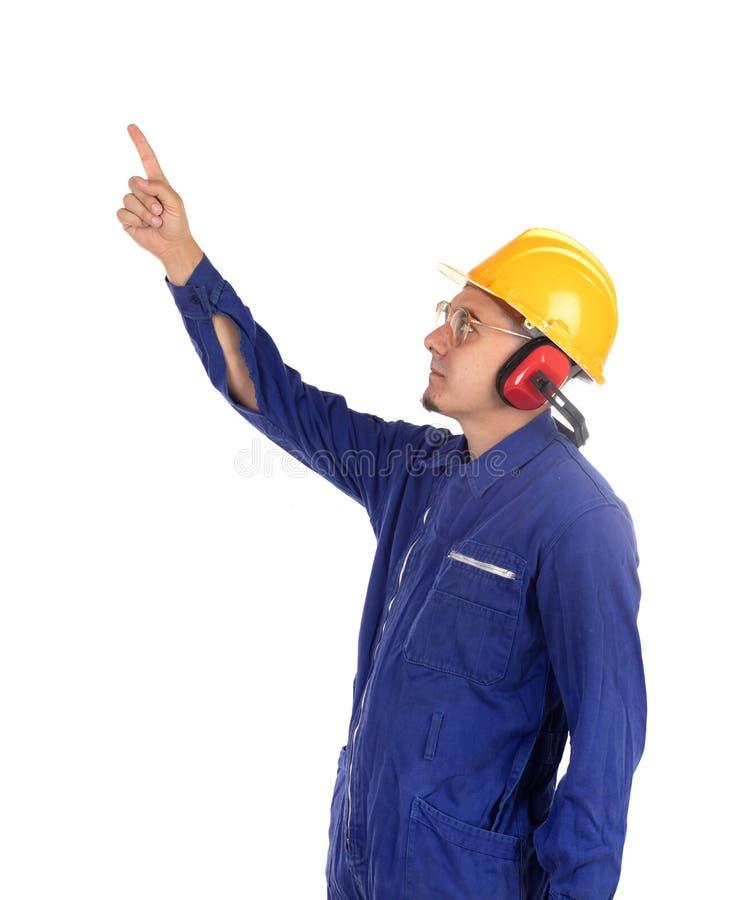 有黄色盔甲的建筑工人指向用他的手的 免版税库存图片